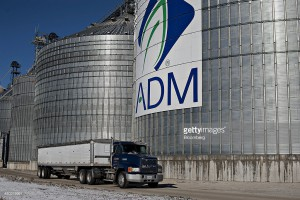 A grain truck passes an Archer Daniels Midland Co. (ADM) logo on the side of a grain storage bin at an ADM grain elevator in Niantic, Illinois, U.S., on Tuesday, Nov. 12, 2013. Photographer: Daniel Acker/Bloomberg